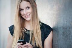 Menina que usa o telefone esperto Fotografia de Stock