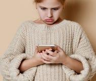 Menina que usa o telefone esperto da pilha, foto de stock