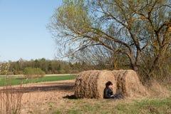 Menina que usa a parte superior do rega?o entre a natureza Tempo em linha A menina est? sentando-se perto de um feno no campo fotos de stock