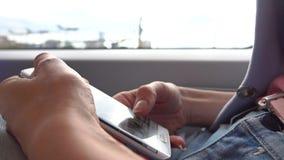 Menina que usa seu smartphone no trem Batida no écran sensível do dispositivo vídeo do close up 4K vídeos de arquivo