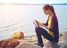 Menina que usa a tabuleta digital no mar imagens de stock