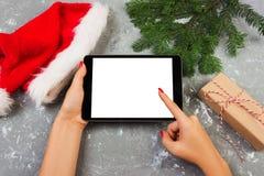 Menina que usa a tecnologia da tabuleta na casa, pessoa que guarda o computador na decoração do Natal do fundo, mãos fêmeas que t foto de stock