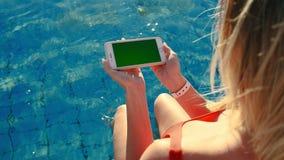 Menina que usa a tela horizontal do verde do telefone celular ao relaxar perto da piscina Mãos que guardam o cromo do smartphone vídeos de arquivo