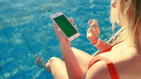 Menina que usa a tela vertical do verde do telefone celular ao relaxar perto da piscina Mãos que guardam a chave do cromo do smar filme