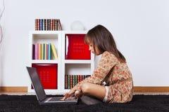 Menina que usa um computador portátil Fotos de Stock