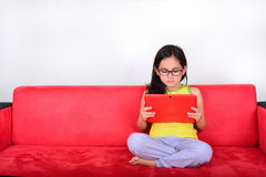 Menina que usa um PC da tabuleta em casa Foto de Stock Royalty Free