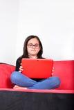Menina que usa um PC da tabuleta em casa Foto de Stock