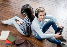 Menina que usa um smartphone e um menino que usa uma tabuleta nos fones de ouvido que escutam a música Fotos de Stock Royalty Free