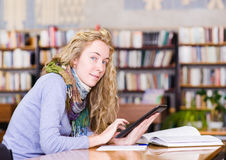Menina que usa um tablet pc em uma biblioteca Foto de Stock Royalty Free