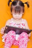 Menina que usa um taplet Fotografia de Stock Royalty Free