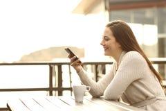 Menina que usa um telefone esperto em férias imagem de stock royalty free