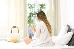 Menina que usa um telefone esperto em uma cama nas férias imagem de stock royalty free