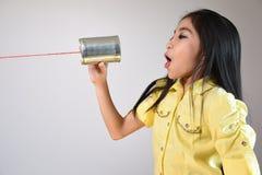 Menina que usa uma lata como o telefone imagem de stock royalty free