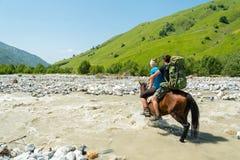 Menina que vadeia o rio perigoso a no cavalo, rio de Adischala, Adishi, Svaneti, montanhas de Cáucaso, Geórgia fotos de stock royalty free
