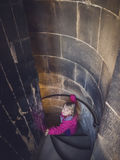 Menina que vai abaixo das escadas espirais Foto de Stock