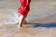 A menina que vai na água com os pés descalços Foto de Stock