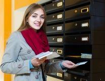 Menina que verifica a correspondência na entrada fotografia de stock