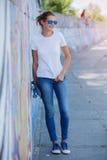 Menina que veste o t-shirt branco vazio, calças de brim que levantam contra a parede áspera da rua Imagens de Stock Royalty Free