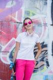 Menina que veste o t-shirt branco vazio, calças de brim que levantam contra a parede áspera da rua Imagem de Stock