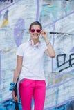 Menina que veste o t-shirt branco vazio, calças de brim que levantam contra a parede áspera da rua Imagem de Stock Royalty Free