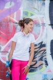 Menina que veste o t-shirt branco vazio, calças de brim que levantam contra a parede áspera da rua Fotografia de Stock