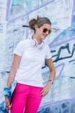 Menina que veste o t-shirt branco vazio, calças de brim que levantam contra a parede áspera da rua Fotos de Stock Royalty Free