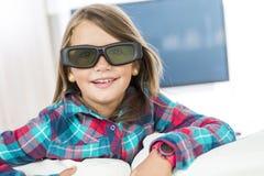 Menina que veste os vidros 3D e que olha a televisão Fotografia de Stock Royalty Free