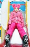 A menina que veste a roupa cor-de-rosa brilhante joga no campo de jogos no inverno Imagens de Stock