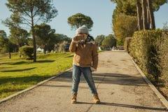 Menina que vestem a capota cinzenta e calças de brim que tomam imagens com a Foto de Stock Royalty Free