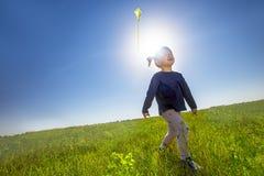 Menina que voa um papagaio em um prado verde imagens de stock