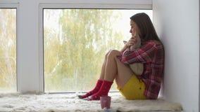 menina Quebrado-hearted que olha através da janela vídeos de arquivo