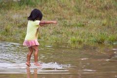 A menina Quechua salta playfully na água fotografia de stock