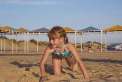 A menina rasteja na areia da praia Fotos de Stock