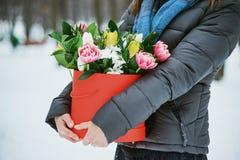 A menina realiza em sua caixa de presente vermelha das mãos com as flores bonitas do ramalhete como um presente para o dia do ` s Foto de Stock Royalty Free