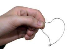 A menina realiza em sua mão um coração do brinco Foto de Stock Royalty Free