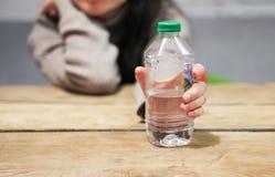 A menina realiza em sua mão uma garrafa da água na tabela foto de stock