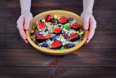 A menina realiza em sua placa de madeira das mãos com a farinha de aveia bonita do prato com um fruto fresco foto de stock royalty free