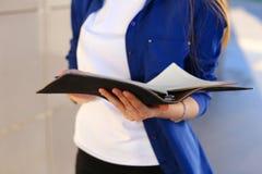 A menina realiza no diário das mãos e no caderno preto com folhas foto de stock royalty free