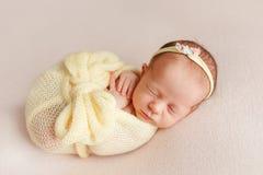 Menina recém-nascida de sono bonito com uma atadura em sua cabeça envolvida dentro fotos de stock