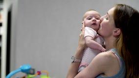 A menina recém-nascida pequena encontra-se em sua ucha com brinquedos vídeos de arquivo