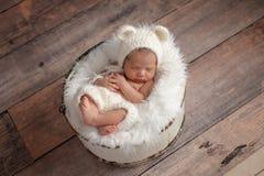 Menina recém-nascida que veste um chapéu do urso branco imagem de stock