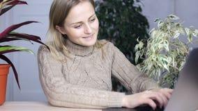 A menina recebe uma mensagem e responde-lhe felizmente rapidamente datilografando o texto em um portátil vídeos de arquivo