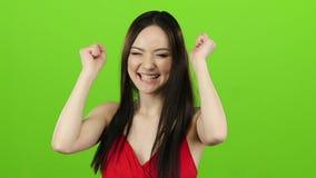A menina recebeu uma vitória grande, ela está feliz com sua vitória Tela verde Movimento lento vídeos de arquivo