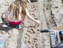 A menina recolhe batatas do campo imagem de stock