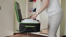 A menina recolhe coisas em uma mala de viagem filme