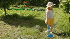 A menina recolhe o ancinho da grama vídeos de arquivo