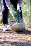 A menina recolhe o lixo P?e-no no saco de lixo O problema da polui??o ambiental Polui??o ecol?gica Problema de imagem de stock