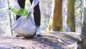 A menina recolhe o lixo P?e-no no saco de lixo O problema da polui??o ambiental Polui??o ecol?gica Problema de fotos de stock