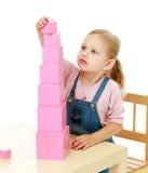 A menina recolhe a pirâmide cor-de-rosa Fotos de Stock