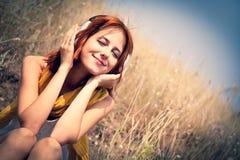 Menina red-haired bonita na grama com auscultadores fotos de stock royalty free